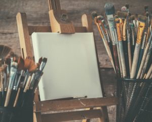 Artistic Equipment: Empty Artist Canvas On Easel And Paint Brush
