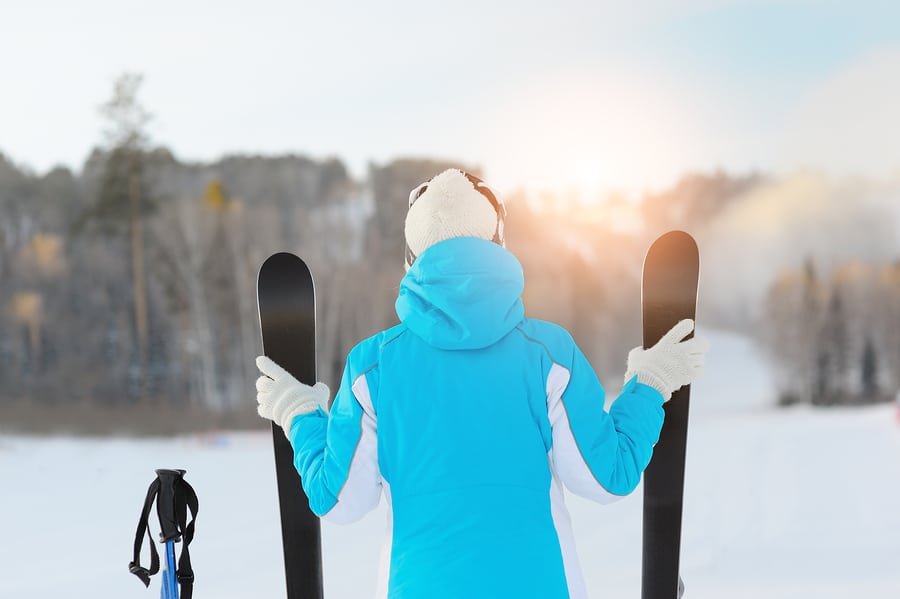 Woman Holds A Pair Of Skiing Looking For Ski Slope.