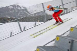winter ski jumper flying down jump