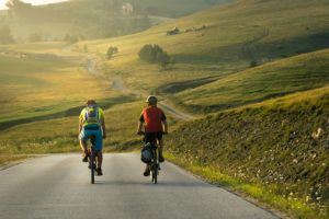 two cyclists on country road with green hills ahead